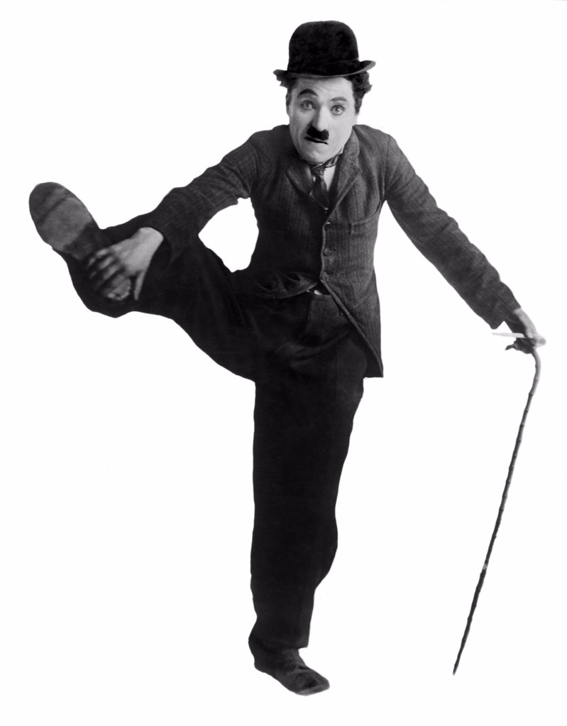 Stock Photo: 4186-794 1910S Circa 1915 Charles Chaplin As The Little Tramp Standing On One Leg Holding Other Up With Hand