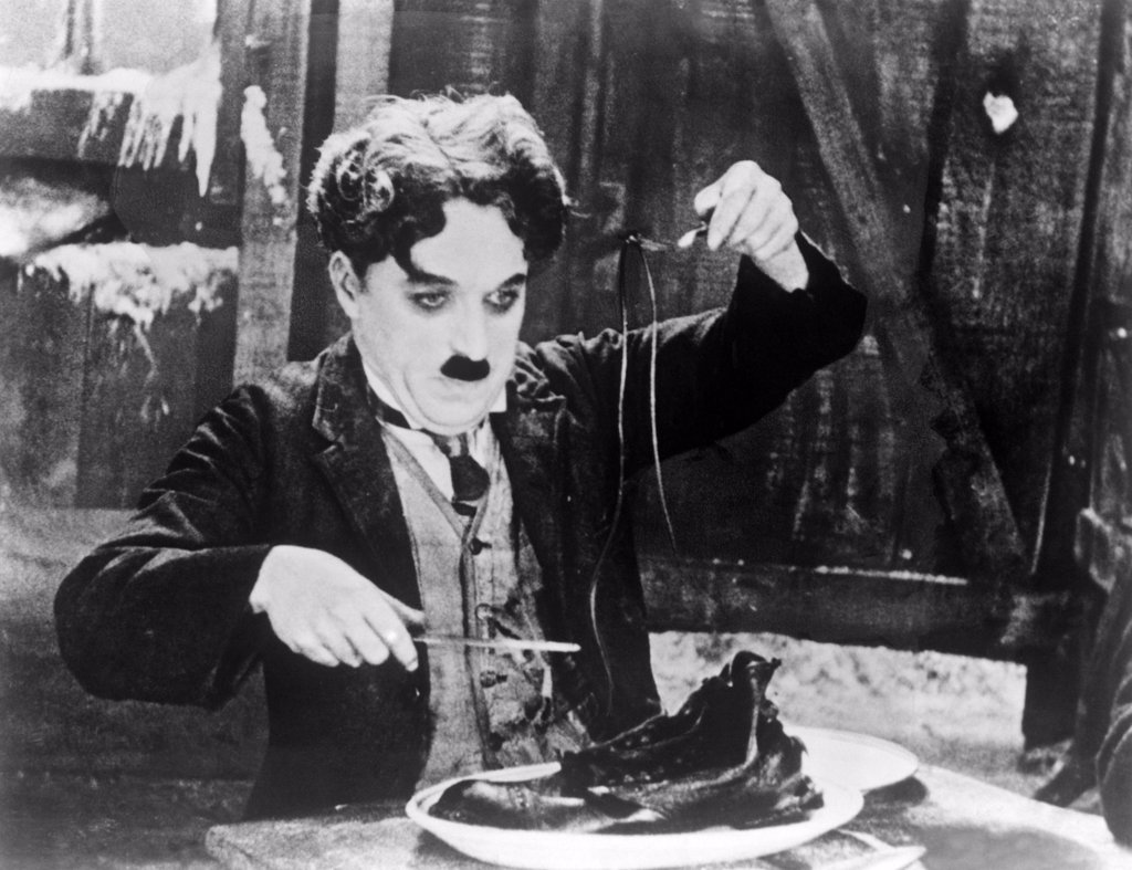 Stock Photo: 4186-798 1920S Charles Chaplin Eating Shoe In Scene From 1925 Film The Gold Rush