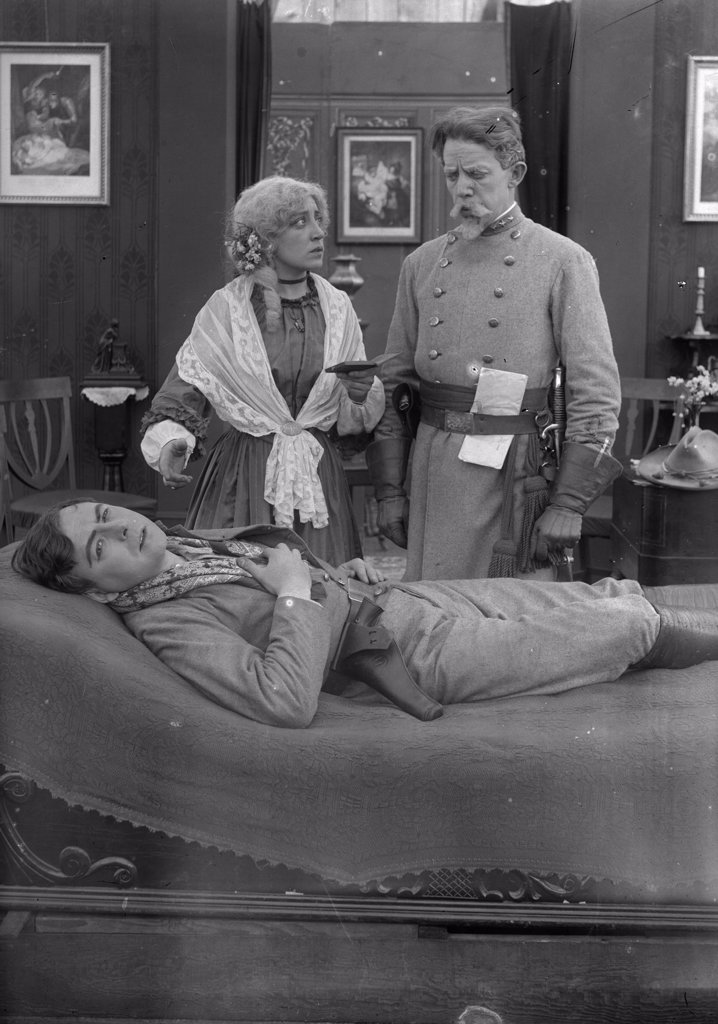 Woman And Civil War Confederate Soldier Watching Over Sick Man Lying On Bed Silent Movie Still : Stock Photo