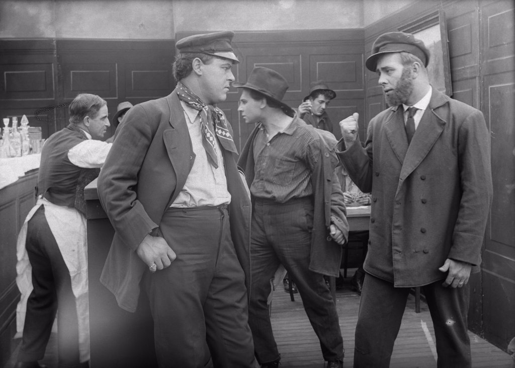 Stock Photo: 4186-809 1910S Men In Seaport Saloon About To Engage In Bar Fight Silent Movie Still
