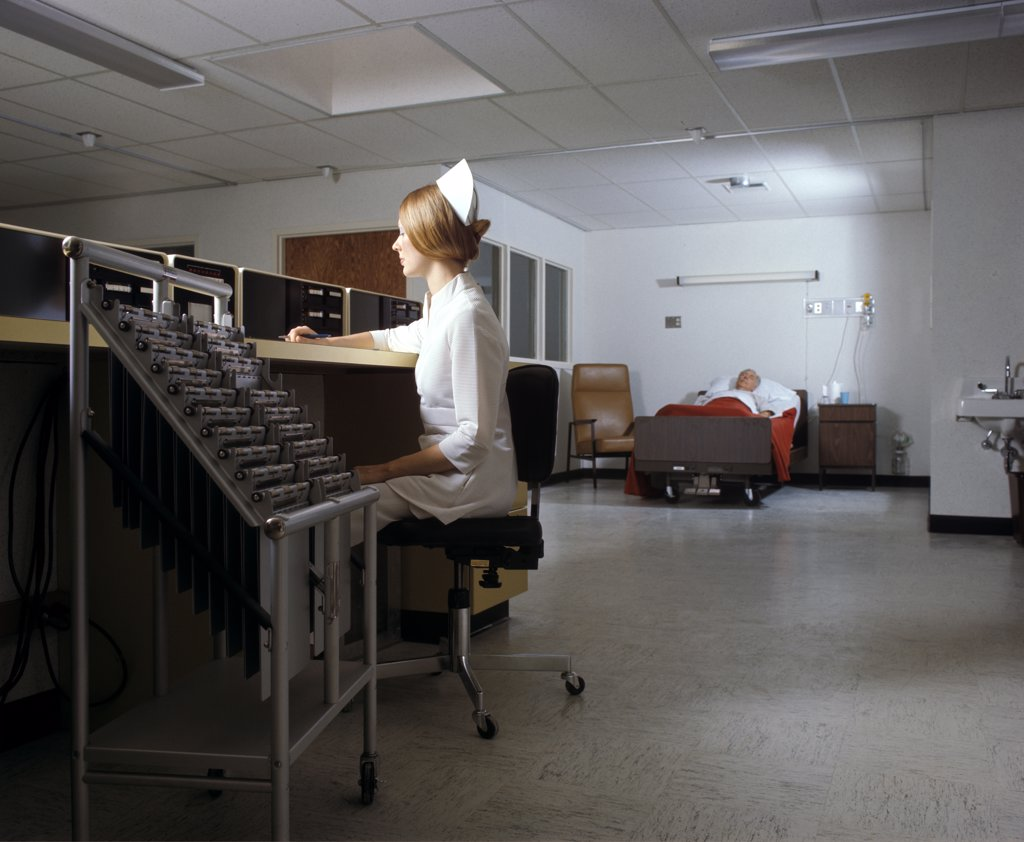 Stock Photo: 4186-8369 1970S Woman Night Nurse Sitting At Nurses Station In Intensive Care Hospital Unit