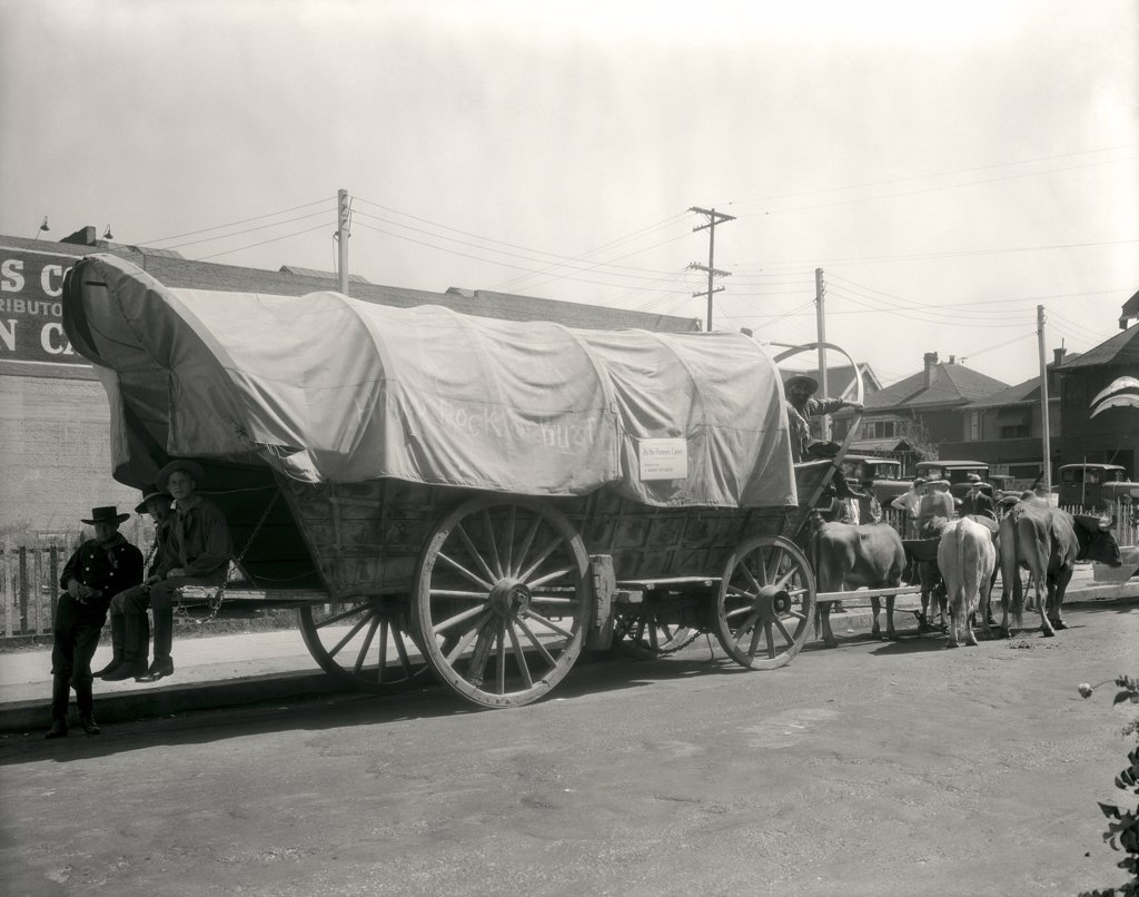 Stock Photo: 4186-839 1920S Ox Drawn Conestoga Covered Wagon Parked Along Street