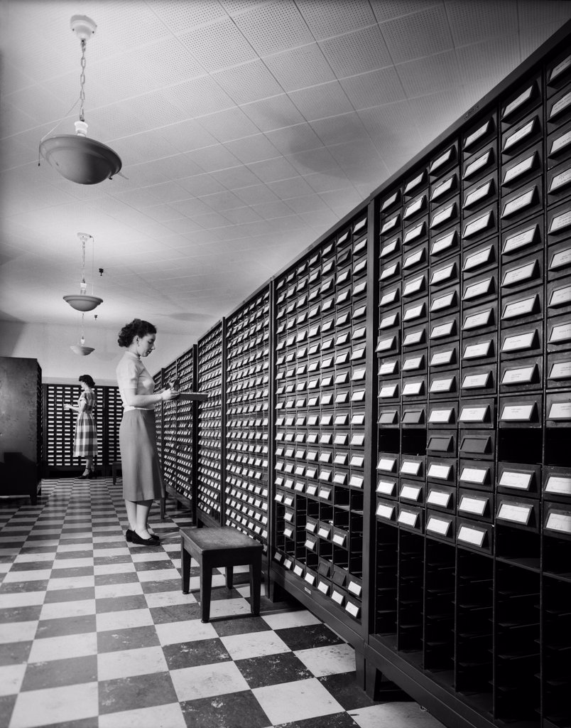 Stock Photo: 4186-856 1950S 1960S Two Young Women Standing Beside Open Drawers Of Computer Punch Card Filing Cabinets