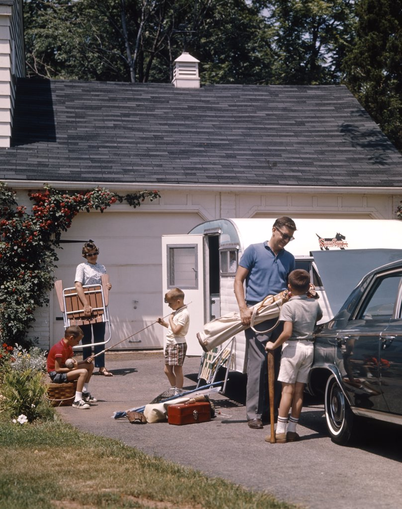 1960S Family Father Mother 3 Sons Loading Car And Trailer For Camping Vacation : Stock Photo