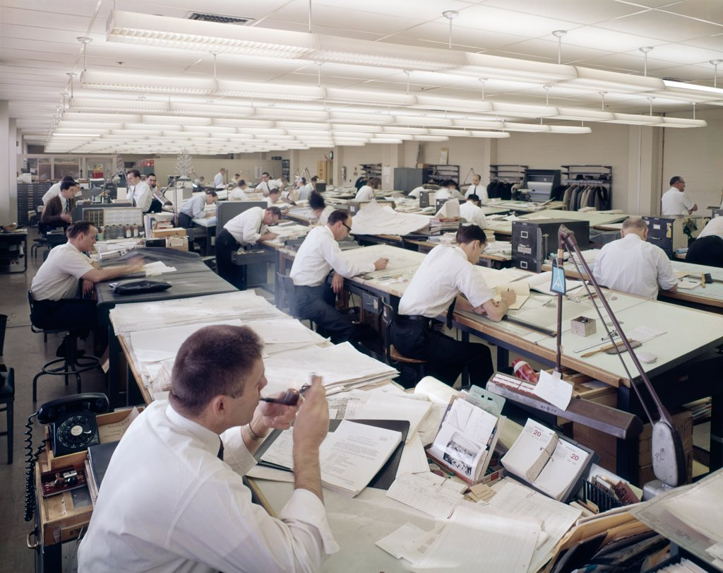 Stock Photo: 4186-8758 1960S Office Full Of Drafting Tables Designer Man Lighting-Up A Pipe Of Tobacco Indoor Industry