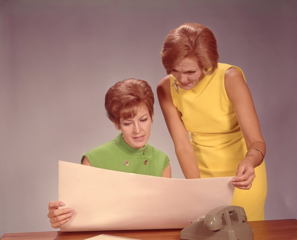1960S Two Women Executives At Desk With Telephone Looking At Worksheet : Stock Photo