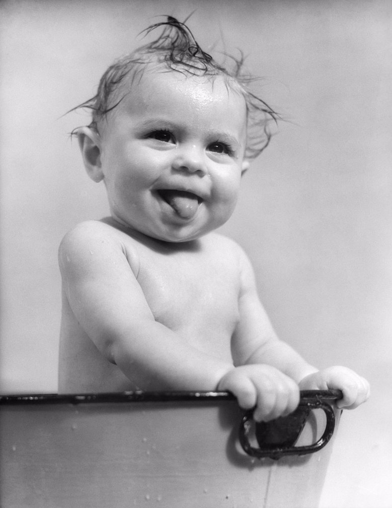1940S 1930S Wet Baby Sitting In Tub Sticking Out Tongue : Stock Photo