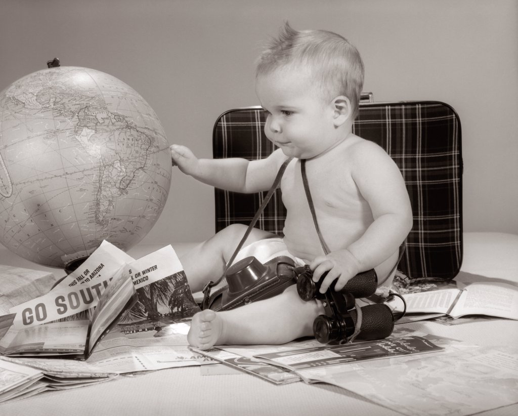Stock Photo: 4186-965 1960S Baby Seated Looking At Globe With Camera Binoculars Suitcase & Travel Brochures