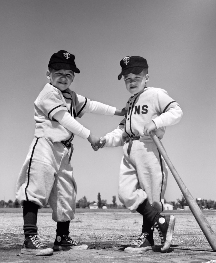 Stock Photo: 4186-971 1960S Pair Of Youth League Players In Uniform Shaking Hands One Holding Bat Looking At Camera