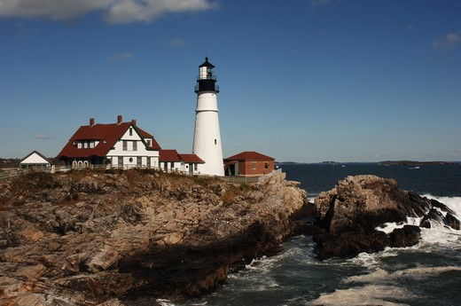 Daytime shot of Portland Head lighthouse with bluffs and Atlantic Ocean : Stock Photo