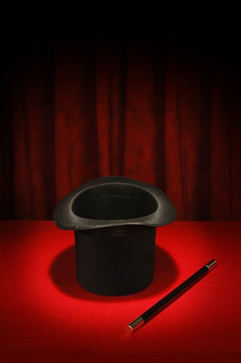 Stock Photo: 4193R-1050 Magician's top hat and magic wand in spotlight on red table cloth and red draped background