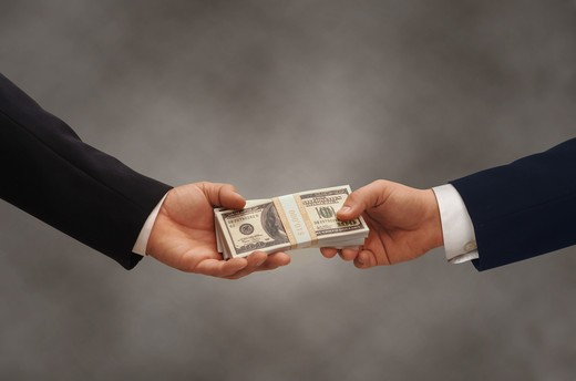Stock Photo: 4193R-1261 Two hands of businessmen passing a stack of dollars