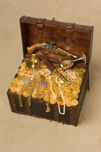 Pirate treasure chest with the lid open brimming with gold coings and pirate paraphernalia on a sandy beach : Stock Photo