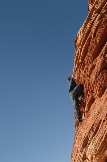 Rock climber climbing a mountain : Stock Photo
