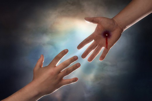Hand of Christ reaching down from heaven to grab the hand of man : Stock Photo