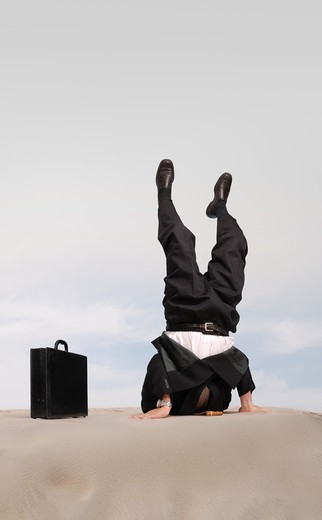 Stock Photo: 4193R-1457 Businessman standing on his head with his head in the sand