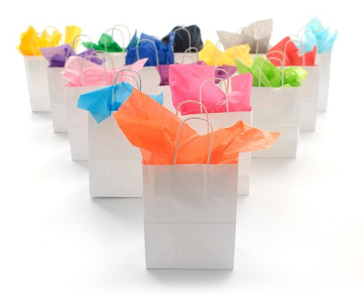 White shopping bags with brightly colored tissues on a white background : Stock Photo