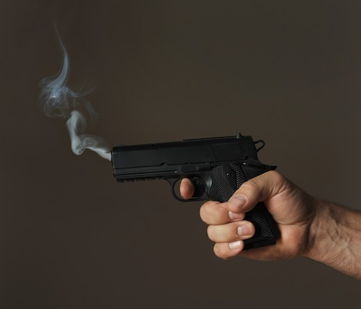 hand holding smoking pistol on dark background : Stock Photo