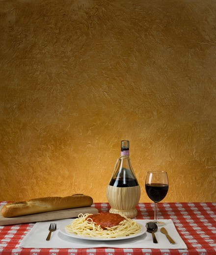 Stock Photo: 4193R-1539 Spaghetti dinner with a baguette and Chianti on a red checkered table cloth with ample background for copy space