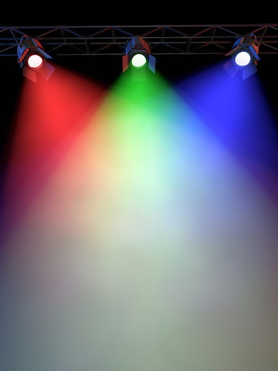 A Stage Light Rack with 3 RG&B Colored Spotlights Shining down towards the middle of the layout in a dark area. : Stock Photo