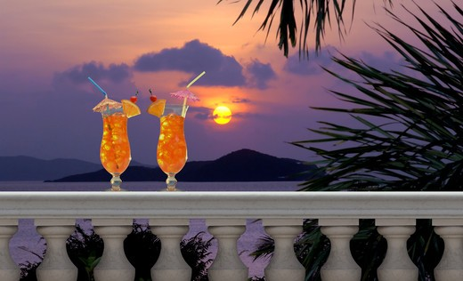 Two tropical fruit drinks with straws and umbrellas on a balcony with a tropical sunset in the background : Stock Photo