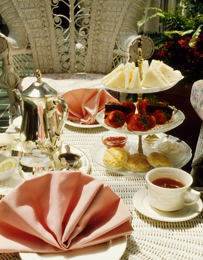 High tea in a garden setting on white wicker furniture : Stock Photo