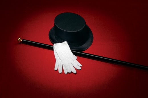 Top hat, white gloves and black cane on red background under a spotlight : Stock Photo