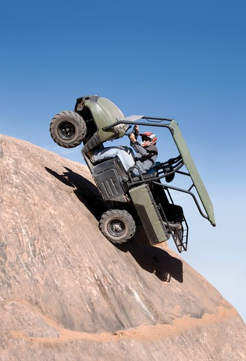 Stock Photo: 4193R-1765 Offroad vehicle climbing up a sheer cliff and falling backwards