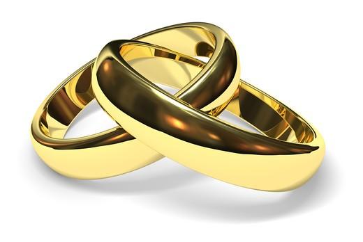 linked gold wedding rings on white background : Stock Photo