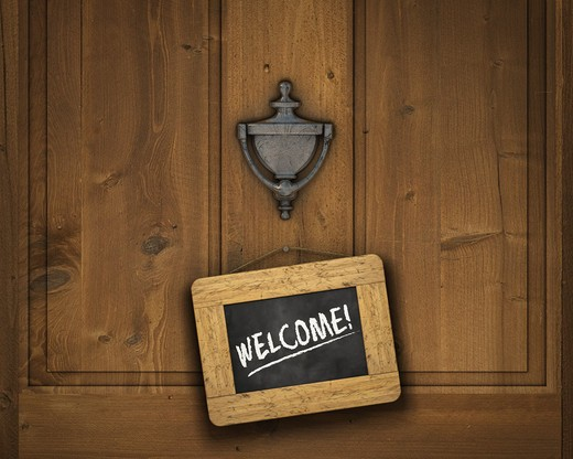 Stock Photo: 4193R-1834 Small chalkboard hanging on a door underneath the door knocker with the word  WELCOME  written in white chalk