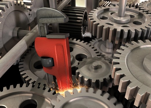 Pipe wrench caught in a gear assembly creating sparks : Stock Photo