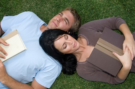Attractive, young couple lying in the grass with books : Stock Photo