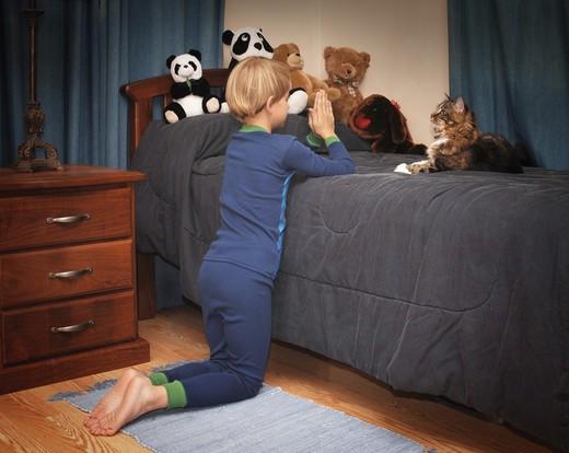 boy kneeling at bedside saying prayers in pajamas : Stock Photo