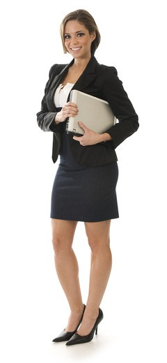 Young attractive professional businesswoman standing on a white background holding a laptop : Stock Photo