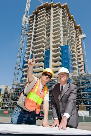 Stock Photo: 4193R-1995 Building developer supervising construction of a hirise with the construction foreman at the job site