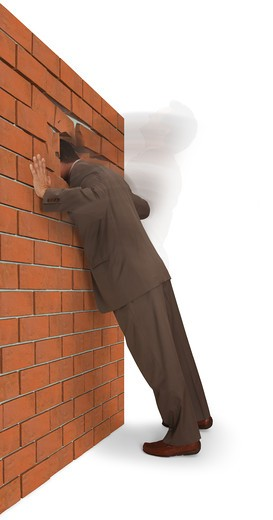 Man slamming his head into a brick wall, isolated on a white background : Stock Photo
