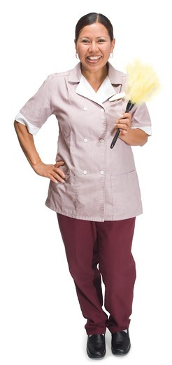 Female hotel maid standing on a white background : Stock Photo