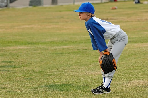 Stock Photo: 4193R-2086 A young boy as catcher in the outfield in baseball youth league
