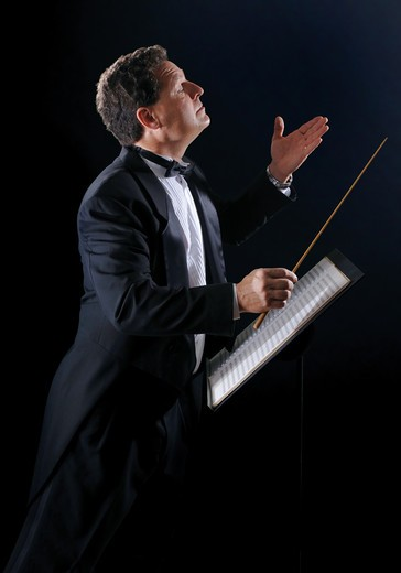 Stock Photo: 4193R-2122 A photo of a music conductor wearing a tuxedo, conducting an orchestra on a black background