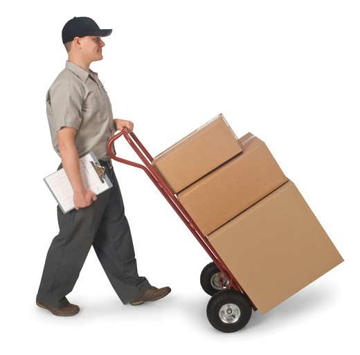 Delivery man pushing hand truck with boxes, isolated on a white background with clipping path : Stock Photo