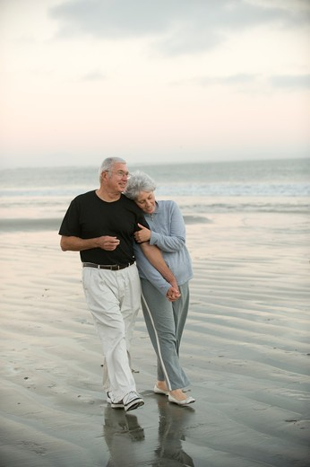 Senior couple walking the beach : Stock Photo