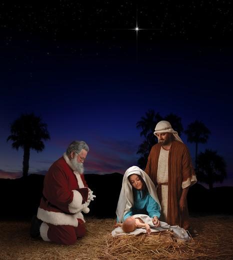 Christmas nativity scene with Santa Claus kneeling before Jesus, Mary & Joseph : Stock Photo