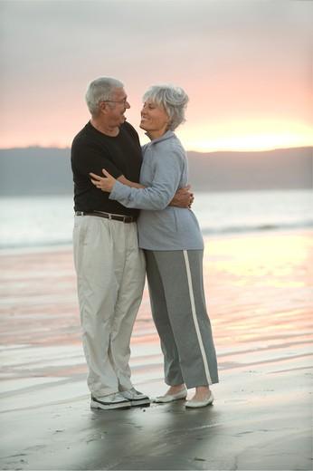 Senior couple hugging on the beach at dusk : Stock Photo
