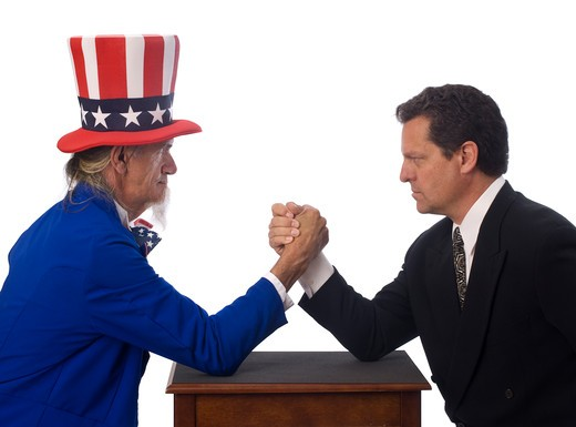 Stock Photo: 4193R-2243 Uncle Sam arm wrestling with a businessman on a white background
