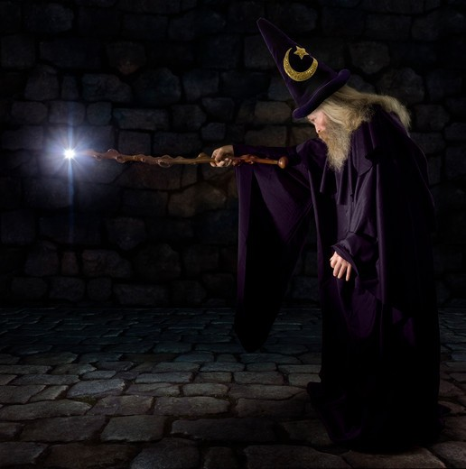 Wizard in a purple robe and wizard hat casting a spell with his wand : Stock Photo