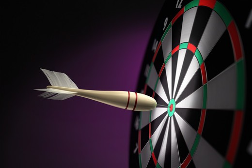 Stock Photo: 4193R-308 A classic wooden dart stuck on the bullseye of the dartboard
