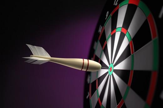 A classic wooden dart stuck on the bullseye of the dartboard : Stock Photo