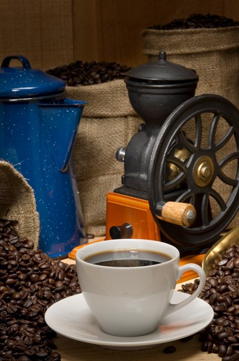 Coffee cup propped with coffee pot, coffee beans, burlap bags of coffee and a vintage coffee grinder : Stock Photo