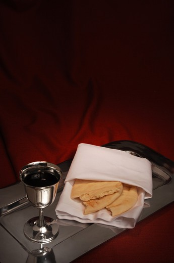 Stock Photo: 4193R-445 communion cup and bread on red fabric