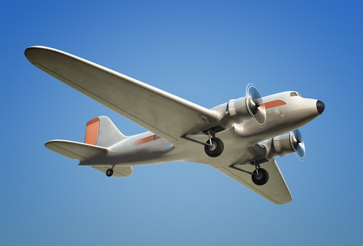 A Shot of a DC3 airplane in flight against a blue sky : Stock Photo